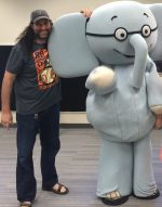 Jason M. Poole standing with a person in an Elmore the Elephant costume