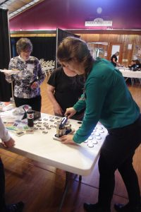 STLS Staff Member Alex demonstrates how the Button Maker works at the STLS Annual Meeting.